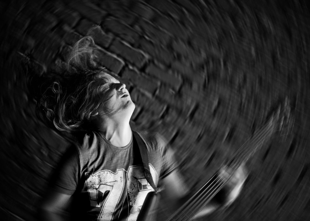 music, radial, play, bass, guitar, black and white, long hair, wall, euphoria, 50mm, natural light, Mike Danilov