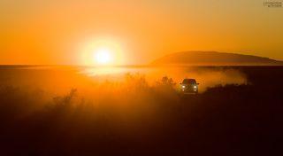 машина поднимает дорожную пыль, создавая интересные условия для закатной фотосессии.