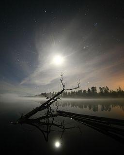Убывающая, но еще яркая Луна создавала мистическую атмосферу, освещая дымку над водной гладью ....