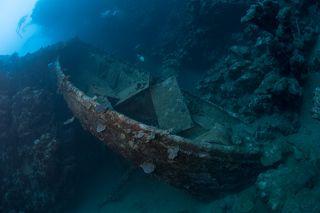 Рядом с кораблем лежит спасательная шлюпка.