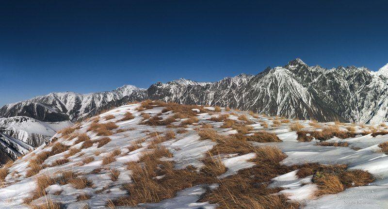 горы, Грузия, Кавказ, Казбеги, трава, зима, снег, горная местность, склон, обрыв, голубое небо Казбегиphoto preview