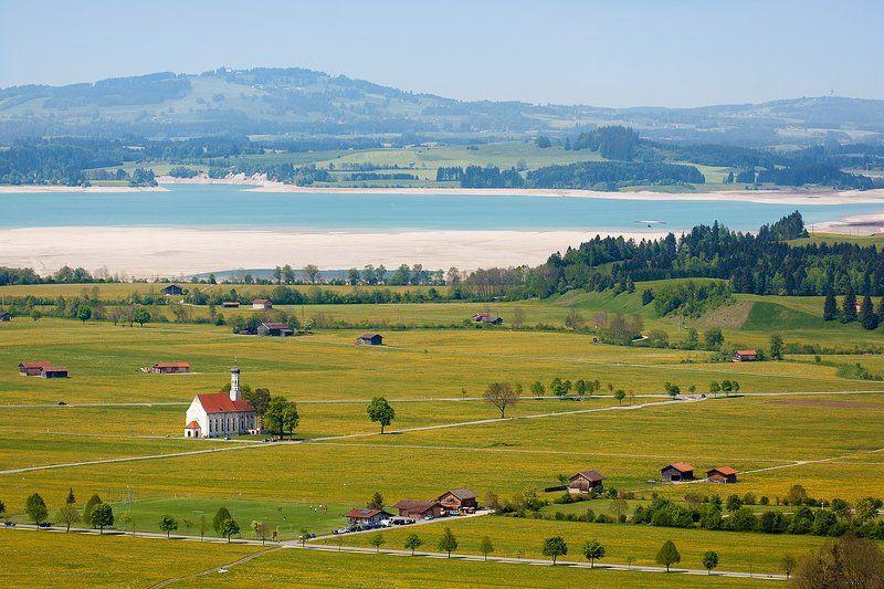 фотография с полем одуванов, дорожками, озером, церквушкой Colomanskirche и одиноким дельтапланеристомphoto preview