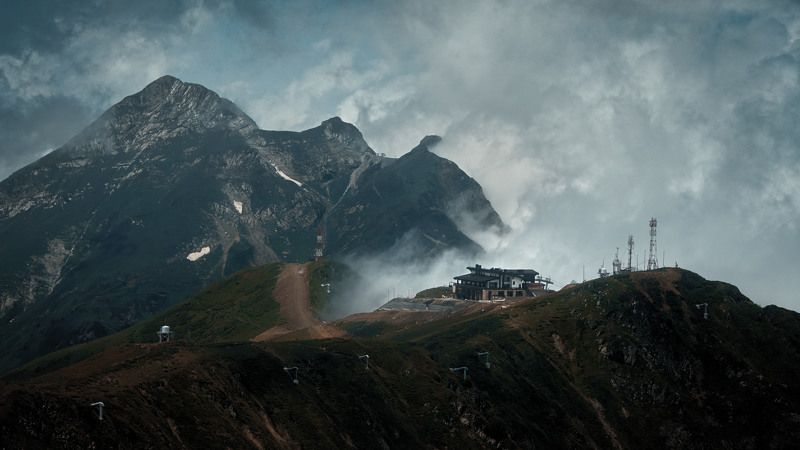 mountains, mountain, rocks, cliff, building, station, sky, clouds, fog, antenna, snow, grass, landscape, road, hills, cinematic, cine, film, filmlook, colors, colorgrade, colorgrading, shot, still, frame, sony, a6300, sochi, caucasus, nature Station in the mountainsphoto preview