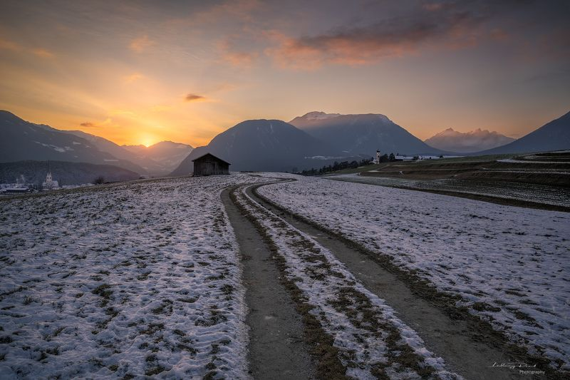 acres, agicutural building, agriculture, alps, austria, austrian alps, bend, bending road, church, clouds, evening, evening glow, farmhouse, fog, foggy, forest, gravel road, hey barn, hill, hills, houses, landscape, meadows, meandered, meandered road, mie Just Beyond the Sunsetphoto preview