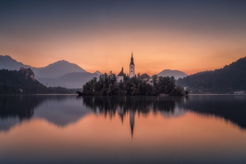 before sunrise, bled, blue, blue hour, calm waters, calmness, castle, church, church tower, cliff, clouds, forest, hills, island, lake, lake bled, lights, morning, mountain range, mountains, outdoors, reflections, rock, serenity, silence, sky, slovenia, s Awakening at Lake Bledphoto preview