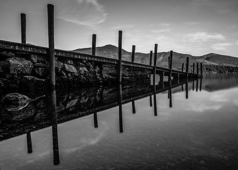 water reflection monochrome england lake mountains sky stones rocks rock stone uk blackandwhite white black contrast photography sky clouds relaxing Jetty reflectionphoto preview