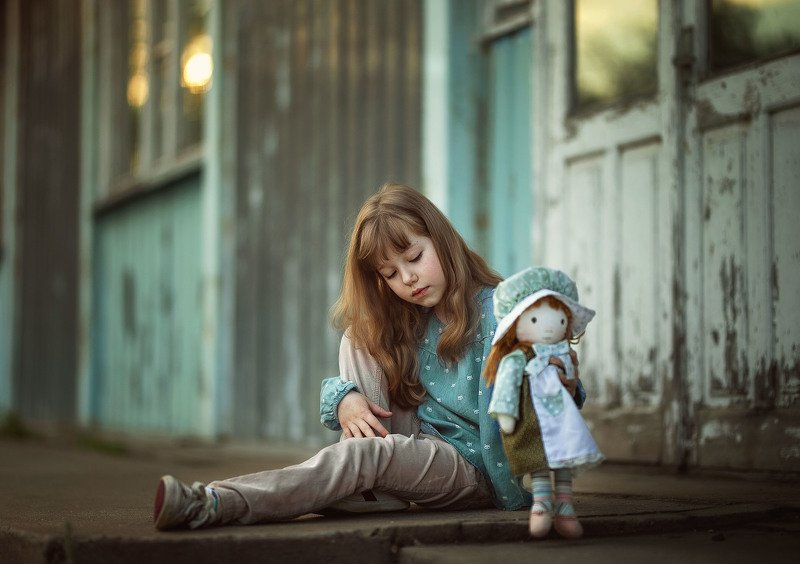 детство девочка игра кукла дочки-  матери улица старый дом photo preview