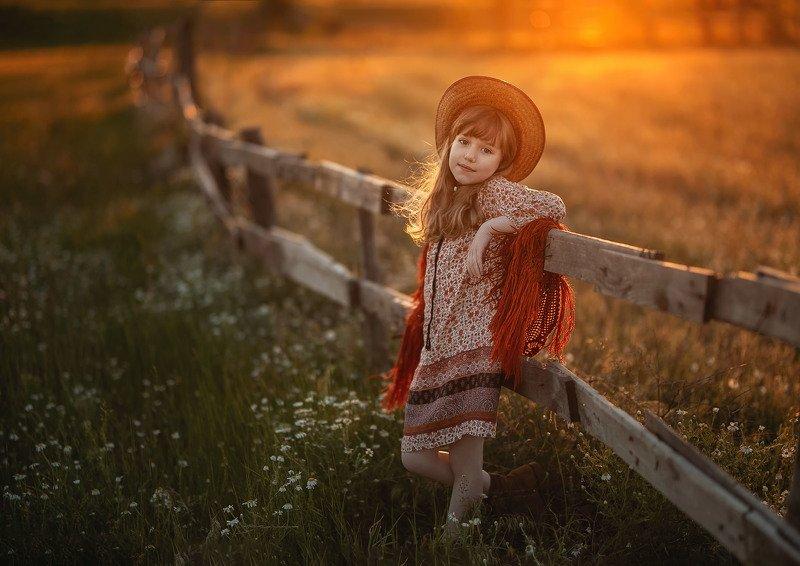 ребенок детство девочка кавбойская шляпа деревянный забор ромашки вечер закат весна ферма на ранчоphoto preview
